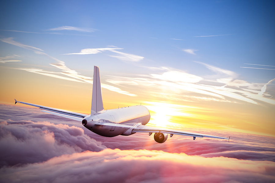Commercial,Airplane,Flying,Above,Clouds,In,Dramatic,Sunset,Light.,Very