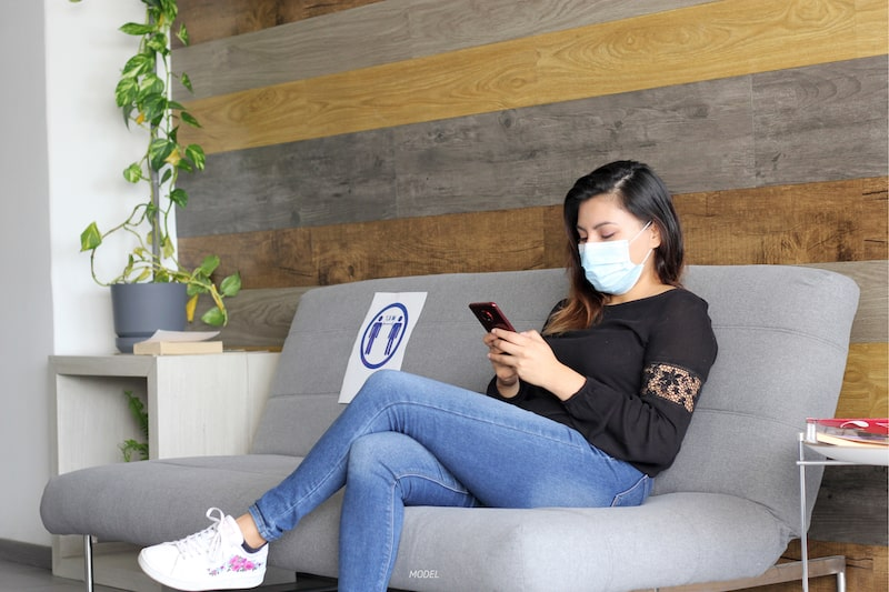 Woman sitting in waiting room, wearing a face mask.